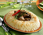 Pilaf rice crown garnished with chicken livers, cumin and chili peppers
