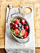Cherries, strawberries and blueberries in a mini casserole and a cup of brown sugar