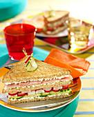 Cream cheese, raw ham, radish and cucumber club sandwiches