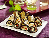 Aubergine rolls garnished with chickpea puree and diced tomatoes