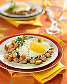 White haricot bean salad topped with a fried egg