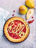 Angeschnittene Birnen-Johannisbeer-Tarte, mit Schriftzug 'hello' verziert