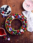 Ländlicher Kranzkuchen mit Blüten und Waldfrüchten