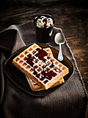 Brussels waffles sprinkled with icing sugar,chocolate sauce and whipped cream