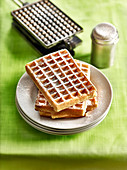 Pile of Brussels waffles sprinkled with icing sugar and a waffle iron