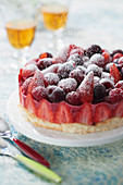 Lychee, raspberry and rose ice cream cake, decorated with fresh red fruits