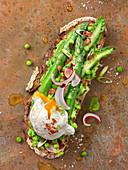 Belegtes Brot mit Erbsenpüree, Spargel, Radieschen, knusprigem Bacon und pochiertem Ei