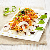 Tagliatelles in tomato sauce with mushrooms, olives and baby spinach