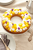 Crown sponge cake decorated with white chocolate mousse, lemon curd and flowers