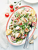 Spaghetti with clams, salicornia, zucchini strips, tomatoes and lemon