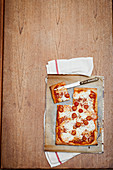 Pizza mit Käse und Tomaten in Stücke schneiden