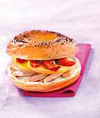 Chicken, cream cheese, apple and sun-dried tomato bagel sandwich