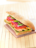 Chicken, tomato, red onion, baby spinach and guacamole ciabatta bread sandwich