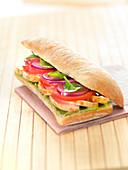 Ciabatta-Sandwich mit Hähnchen, Tomaten, roten Zwiebeln, Babyspinat und Guacamole