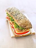 Mohn-Sesam-Brot-Sandwich mit Frischkäse, Tomaten, Emmentaler, Walnüssen und Salat
