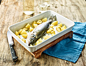 Preparing sea bass and potatoes to be oven-baked