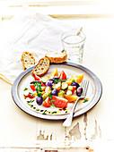 Salat mit Tomaten, Gurke, Oliven, Knoblauch, Schnittlauch und Thymian
