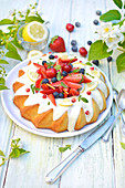 Zitronenkranzkuchen mit Sahne und frischen Waldfrüchten
