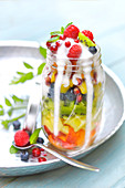 Fresh fruit salad in a jar with runny yoghurt