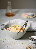 Rice noodles with ginger, shredded salmon and black sesame seeds