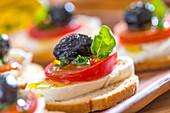 Belegtes Brot mit Tomate, Mozzarella und Olive (Detail)