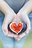 Hands holding a heart-shaped sliced fig