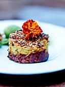 Vegetarisches Hachis mit Kürbis-Kichererbsen-Stampf, Zwiebeln, Kartoffelpüree und Leinsamen