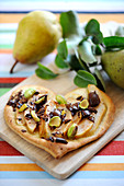 Pear,pistachio and chocolate heart-shaped sweet pizza