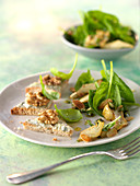 Baby spinach and sliced artichoke salad with Roquefort butter on toasts