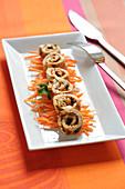 Seasoned turkey rolls on a bed of small carrot stciks