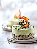 Small avocado and lime cheesecake topped with a shrimp and sprinkled with black sesame seeds