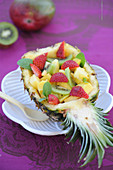 Exotic fruit salad served in a pineapple skin
