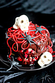Chocolate,pistachio cream and cherries glac? cake decorated with sugar paste sculls and spaghetti sweets