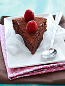 Slice of chocolate and almond cake topped with fresh raspberries