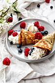 Pancake cones garnished with whipped cream and summer berries