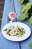 Tagliatelles with flowers and thinly sliced courgettes outdoors