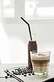 Kaffeegetränk in Flasche und ein Glas Cappuccino