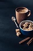 Tasse Kaffee mit braunen Zuckerwürfeln und Zimt