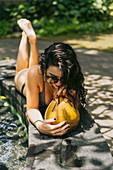 Junge Frau in Bikini mit Sonnenbrille trinkt tropischen Cocktail am Pool