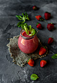 Delicious detox strawberry smoothie on rustic wooden board