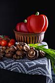 Stillleben mit Pilzen, Paprika, Lauchzwiebeln und Tomaten
