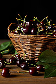 Ripe harvested cherries in rustic basket with leaves on wooden table and on black