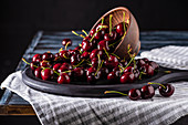 close up view of pile of red ripe cherries in bowl on cutting board on wooden table