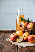 Glass bottle of apple juice and apples in basket on wooden tabletop