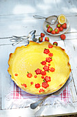 Thin lemon curd pie decorated with strawberries