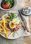 Steak-Tartar mit gekochtem Ei, Avocado und Pommes frites