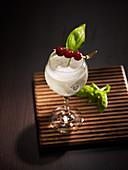 Prickelnder Kokos-Cocktail mit Kirschspieß und Basilikumblatt