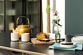 Kürbiskuchen und Teekanne mit Bechern auf Tisch