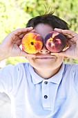 Kind hält sich zwei Pfirsiche vor die Augen