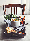Karottencremesuppe mit Kurkuma und Sahne auf Holztablett